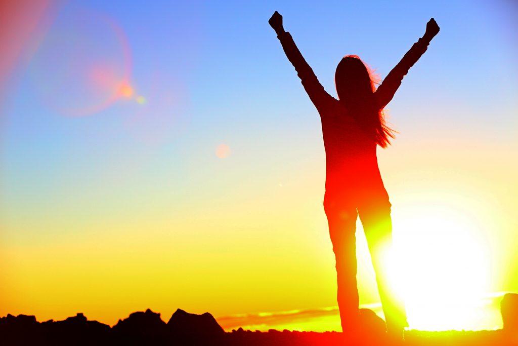 Bilde: Jente i solnedgangen, med armene over hodet.