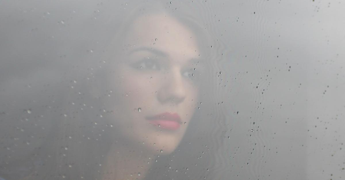 Bilde: Kvinne ser gjennom tåkete vindu.