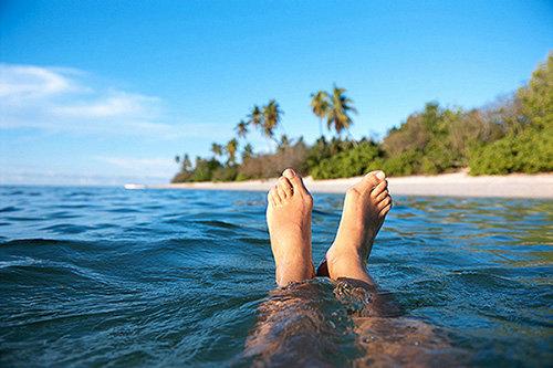 Bilde: Bilde av føtter, flytende i havet med en middelhavsøy i bakgrunnen.