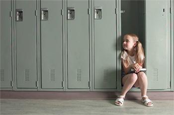 Bilde: Skolejente sitter i gangen i skolen.
